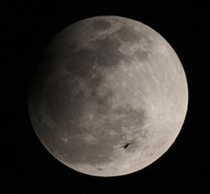 Die Finsternis mit einer Flugzeugsilhouette im Vordergrund. 22:10 MESZ, 1000mm-Teleobjektiv bei f/10, Canon EOS 1100D, ISO 400, 1/400s. [Ignacio Llorens]