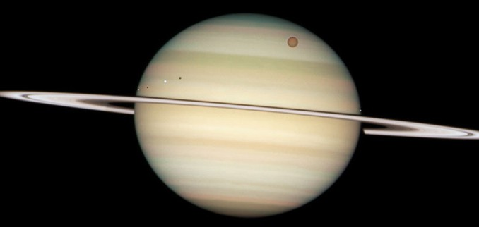 Eine extrem seltene Konstellation der Saturnmonde, wie sie nur in der Nähe der Tag- und Nachtgleichen beobachtet werden kann: Gleich vier Monde stehen auf dieser Hubble-Aufnahme vom 24. Februar vor der Scheibe des Planeten. Von links Enceladus, Dione, der riesige orange Titan und Mimas. Da das Sonnenlicht etwas von links kommt, kann man rechts von Enceladus und Dione auch die Schatten der Monde sehen. [NASA, ESA und das Hubble Heritage Team (STScI/AURA)]