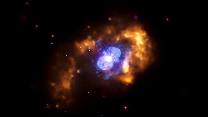 Eta Carinae, der wohl mysteriöseste veränderliche Stern am Himmel, in einer aktuellen Aufnahme im Röntgenlicht und sichtbaren Spektralbereich. Die Röntgendaten des Satelliten Chandra in gelb und orange zeigen Strahlung, die vom Stern emittiert wird und mit der umgebenden Materie kollidiert. Blau abgebildet ist der den Stern umgebende Nebelkokon, der beim Ausbruch von 1843 entstandene Homunculus-Nebel. [NASA/ STScI/CXC/GSFC/M.Corcoran et al]
