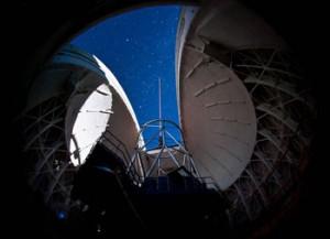 So funktionieren die Laser-Sterne von GeMS: Eine Aufnahme durch ein Teleskop zeigt fünf helle Punkte, die die Laser in einer 90 km hohen Atmosphärenschicht erzeugen. Dort wird Natrium zum Leuchten angeregt; die Strahlen in der Atmosphäre darunter sieht man nur, weil das Licht hier an Schwebeteilchen gestreut wird. [Gemini Observatory/AURA]