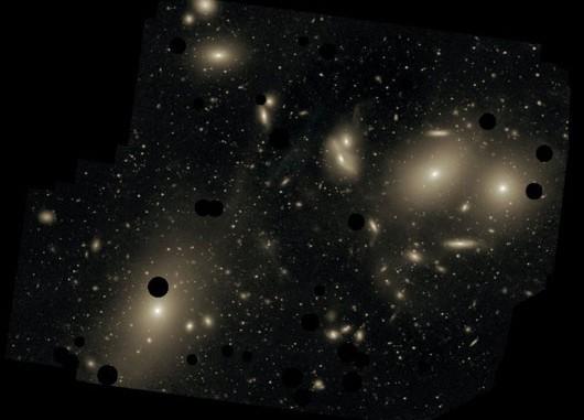 Eine sehr tiefe Aufnahme des Virgo-Galaxienhaufens (bei dem helle Vordergrundsterne ausgeblendet wurden) mit dem Burrell-Schmidt-Teleskop zeigt diffuses »Intra-Cluster-Licht« zwischen den Galaxien: Hier sind während der turbulenten Geschichte des Haufens Sterne gelandet, die nicht mehr an einzelne Galaxien (wie M 87, unten links) gebunden sind. Dieses Licht überlappt sich oft mit den stellaren Halos der Galaxien — aber eingelagerte Planetarische Nebel erlauben die Unterscheidung. [Chris Mihos]