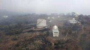 Das Siding Spring Observatory am Morgen danach: Die Luft ist noch voller Rauch, viel Vegetation und einige normale Gebäude sind verbrannt – aber alle Teleskopkuppeln stehen bis auf etwas Ruß noch unbeschadet da. [New South Wales Rural Fire Services]