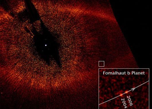 Fomalhaut, fotografiert von der »Advanced Camera for Surveys« des Hubble Space Telescope, mit dem neuen Planeten Fomalhaut b. Das kleine weiße Kästchen zeigt die Lage des Planeten, der Ausschnitt die Bewegung, die die Planetennatur verriet. Fomalhaut selbst ist auf dem Bild nicht zu sehen, da er wie bei der Koronabeobachtung der Sonne ausgeblendet werden muss, um die schwachen Strukturen in seiner Umgebung zu sehen. Der rote Punkt links unten ist ein Hintergrundstern. [NASA, ESA, P. Kalas, J. Graham, E. Chiang, E. Kite (University of California, Berkeley), M. Clampin (NASA Goddard Space Flight Center), M. Fitzgerald (Lawrence Livermore National Laboratory), und K. Stapelfeldt und J. Krist (NASA Jet Propulsion Laboratory)]