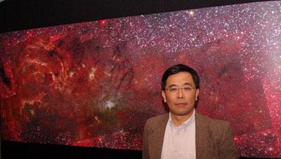 Q. D. Wang von der University of Massachusetts in Amherst vor einem Poster seines infraroten Kompositbildes von der Zentralregion unserer Milchstraße, das aus Aufnahmen der NICMOS-Kamera von Hubble und der IRAC-Kamera des Spitzer Space Telescope zusammengesetzt wurde. [AAS Photo von Kelley Knight Heins]