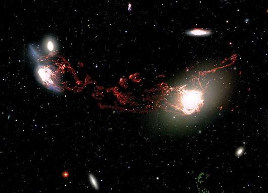 Eine tiefe Aufnahme zeigt die 400000 Lichtjahre langen Filamente, die die Galaxien M 86 (rechts) und NGC 4438 verbinden: Hier strahlt Wasserstoff im H-Alpha-Licht in einer ähnlichen Geschwindigkeit wie die beiden Galaxien. Die (in dieser speziellen Falschfarbdarstellung) grüne Wolke rechts unten bei NGC 4388 ist Wasserstoff mit einer anderen Geschwindigkeit: Diese Galaxie hat mit dem anderen Geschehen nichts zu tun. [Tomer Tal and Jeffrey Kenney/Yale University and NOAO/AURA/NSF]