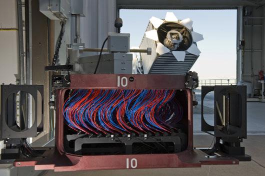Eine der BOSS-Kassetten mit jeweils 1000 Glasfaserkabeln, die das Licht einzelner Galaxien im Gesichtsfeld des SDSS-Teleskops (im Hintergrund zu sehen) zum Spektrographen leiten. [Dan Long, Senior Operations Engineer, Apache Point Observatory]