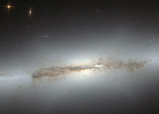 Die Linsen-Galaxie NGC 4710, die Hubbles Kamera ACS von der Seite sieht: Die Sterne des zentralen »Bulge« bilden eine diffuse X-Form, da sie sich auf zur galaktischen Ebene geneigten Bahnen befinden — ein Phänomen, das bei Spiralgalaxien mit engliegenden Armen wie dieser nur selten beobachtet wird. [NASA & ESA]