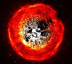 """Ein Hubble-ACS-Bild der Hülle des Kohlenstoffsterns U Cam, der selbst von einer Koronographenblende abgedeckt ist (eine zweite Blende verursacht die kleine Abschattung oben rechts). Das Bildfeld ist 20"""" groß. [Olofsson et al.]"""