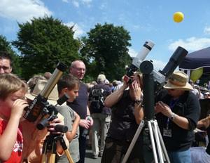 Wanderer auf dem »Ruhrschnellweg« A40 scharen sich während des »Stilllebens« am 18. Juli um Teleskope des Köln-Bonner Astrotreffs, die – am Rande des »Venus«-Tisches des aktionsweiten Sonnensystems – auf die Sonne gerichtet sind. Im Hintergrund ein 3,7m großer Heliumballon, der den Standort des »Sonne«-Tisches markierte. [Daniel Fischer]
