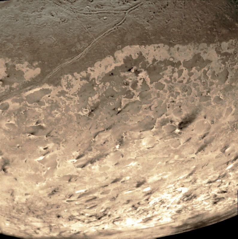Geysire auf Triton, aufgenommen von Voyager 2, 1989. (nachkolorierte Aufnahme) Etwa 50 dunkle Eruptionsfahnen kennzeichnen die Eisvulkane. [NASA]