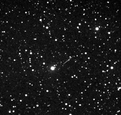 """Kleinplanet (153591) 2001 SN263, 8.2.2008, 21:12–21:32 UT, Norden ist oben, Bildfeld 20'×20'. Bild ist zentriert auf die Sterne, der Kleinplanet beschreibt durch seine rasche Bewegung eine Strichspur. Der Kleinplanet stand hoch am Himmel im Sternbild Auriga (Fuhrmann) und bewegte sich mit 5,2"""" pro Minute nach Südosten (links unten am Bild). 130/484mm-Refraktor, 60 Einzelaufnahmen zu je 10 Sekunden Belichtungszeit, zentriert und addiert mit Astrometrica. [Wolfgang Vollmann]"""