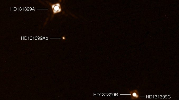 Drei Sterne, ein Planet - auf einer Aufnahme mit der Kamera SPHERE des Very Large Telescope. Der Planet Ab, durch seine Wärmestrahlung sichtbar, kreist um den Stern A, der mit den eng umeinander kreisenden Sternen B und C ein Dreifachsystem bildet. [ESO/K. Wagner et al.]